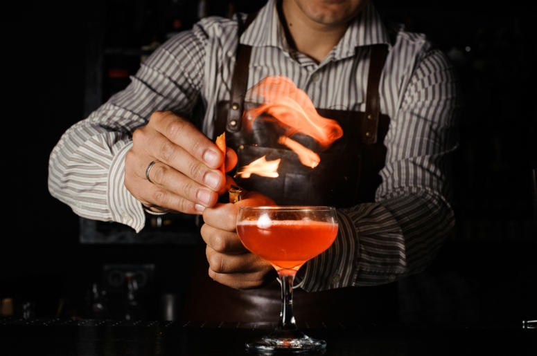 The bartender makes flame above cocktail. Mixologist, alcohol.