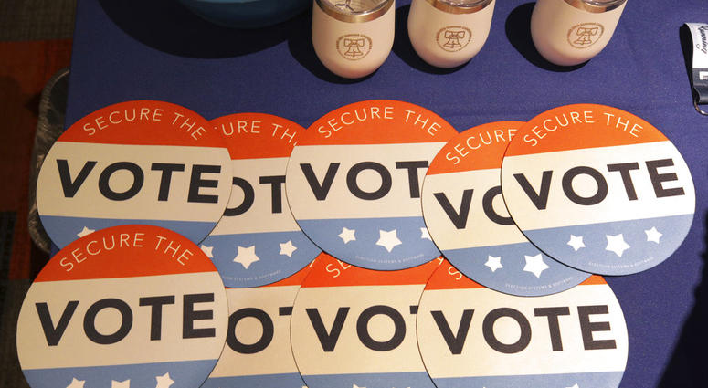 FILE - In this July 14, 2018, file photo, computer mouse pads with Secure the Vote logo on them are seen on a vendor's table at a convention of state secretaries of state in Philadelphia. (AP Photo/Mel Evans, File)