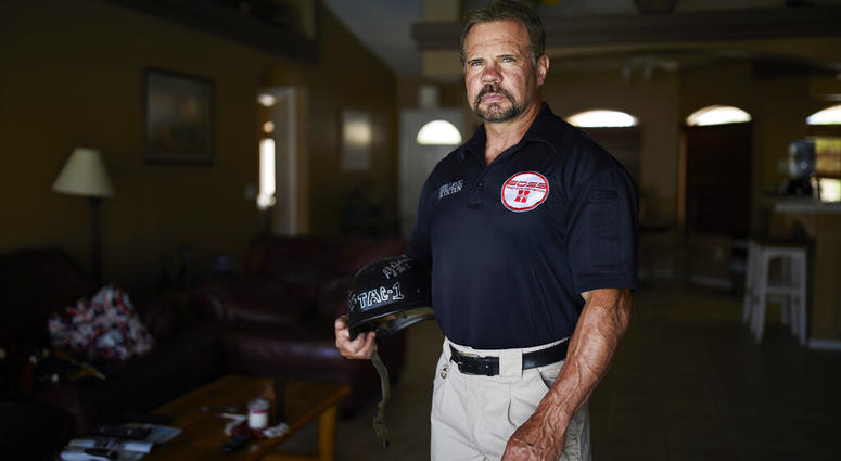 Grant Whitus poses for a portrait at his home in Lake Havasu City, Ariz. Whitus' marriage fell apart a year after he led his SWAT team into Columbine High School's library, where he was the first to find the dead children's bodies. (AP Photo/John Locher)