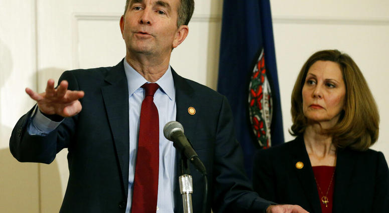 FILE - In this Feb. 2, 2019 file photo, Virginia Gov. Ralph Northam, left, gestures as his wife, Pam, listens during a news conference in the Governors Mansion at the Capitol in Richmond, Va. (AP Photo/Steve Helber, File)