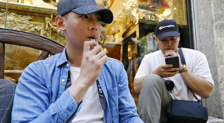 In this Monday, June 17, 2019, photo, Joshua Ni, 24, and Fritz Ramirez, 23, vape from electronic cigarettes in San Francisco.   (AP Photo/Samantha Maldonado)