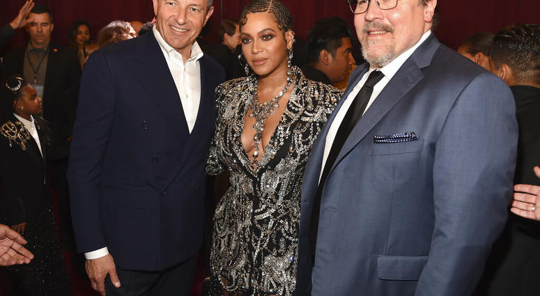 "Bob Iger, left, chairman and CEO of The Walt Disney Company, poses with ""The Lion King"" cast member Beyonce, center, and the film's director Jon Favreau at the premiere of the film. (Photo by Chris Pizzello/Invision/AP)"