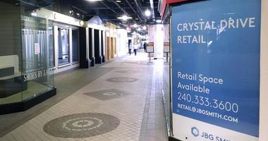 In this Thursday, Nov. 8, 2018, photo, pedestrians walk the underground corridors in Crystal City, Va.  (AP Photo/Matthew Barakat)