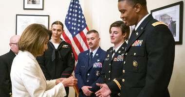 Speaker of the House Nancy Pelosi, D-Calif., left, gives challenge coins to U.S. Army Maj. Ian Brown, right, and other military service members to thank them for their service. (Julio Obscura/Office of the Speaker of the House Nancy Pelosi via AP)