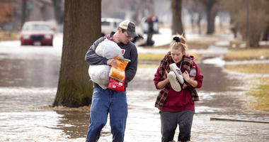 Anthony Thomson, left, and Melody Walton make their way out of a flooded neighborhood Sunday, March 17, 2019, in Fremont, Neb. (Kent Sievers/Omaha World-Herald via AP)