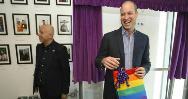 Britain's Prince William, the Duke of Cambridge, reacts to receiving a gift bag from trust chief executive officer Tim Sigsworth, during a visit to the Albert Kennedy Trust. (Jonathan Brady/Pool Photo via AP)