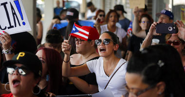 About 200-300 people from the North Texas (Dallas-Fort Worth area) Puerto Rican community gather to protest Gov. Ricardo Rossello outside the Adobo Puerto Rican Cafe in Irving, Texas.  (Tom Fox/The Dallas Morning News via AP)