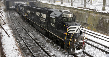 FILE - In this March 3, 2019, file photo a Norfolk Southern freight train passes through the Northside of Pittsburgh as show begins to fall. Norfolk Southern Corp. reports earning on Wednesday, July 24. (AP Photo/Gene J. Puskar, File)