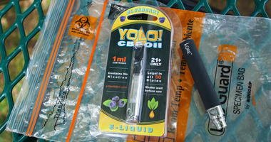 FILE - In this May 8, 2019, file photo, a Yolo! brand CBD oil vape cartridge sits alongside a vape pen on a biohazard bag on a table at a park in Ninety Six, S.C.  (AP Photo/Allen G. Breed, File)