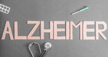 A stethoscope, pills and a disposable syringe on a dark background with the word Alzheimer made out of cardboard. (Dreamstime)