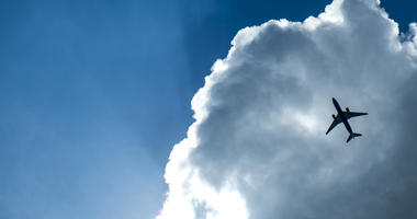 Passenger airplane in the clouds and sunray.(Dreamstime)