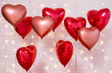 Valentine`s day background - group of red heart shaped balloons over brick wall.