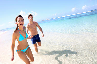 A man and woman in bathing suits at the beach