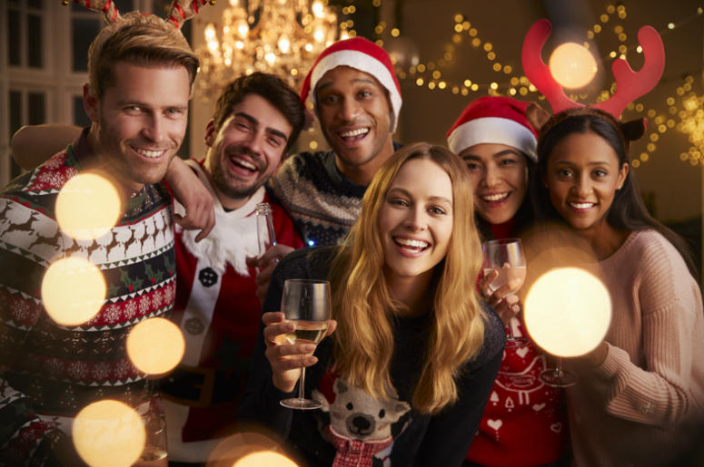Portrait Of Friends In Festive Jumpers At Christmas Party