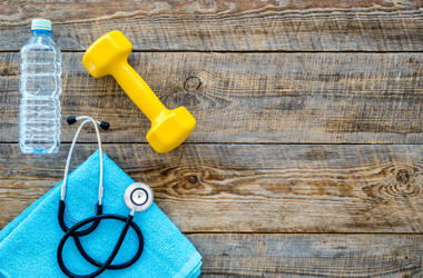 Sport and health. Fitness. Dumbbells and stethoscope on wooden background top view copyspace