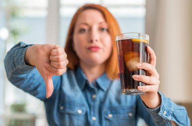 Girl Holding Soda Giving Thumbs Down
