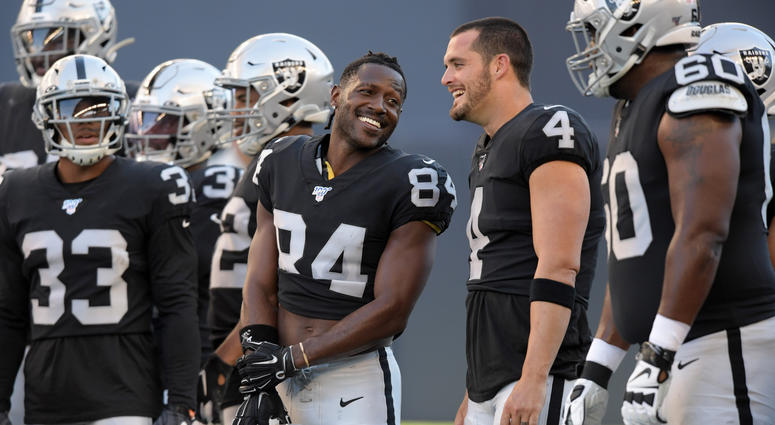 Oakland Raiders wide receiver Antonio Brown (84) and quarterback Derek Carr (4) hold their helmets before a game against the Green Bay Packers at Investors Group Field