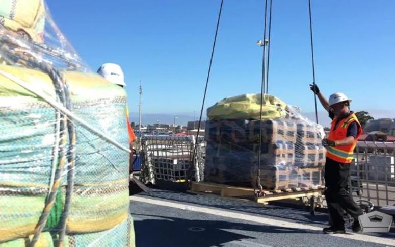 The crew of the Coast Guard Cutter Munro offloads more than 39,000 pounds of cocaine and 933 pounds of marijuana