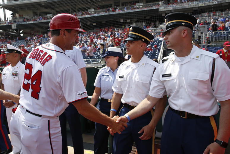 Nationals First Base Coach Tim Bogar greets military members honored before the game