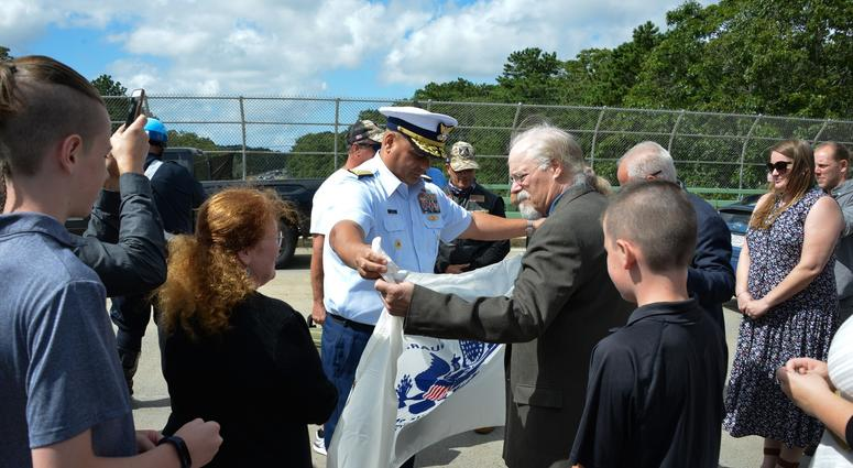 Coast Guard Adm. Andy Tiongson presents Stephen and Bradley Finch with the Coast Guard Ensign