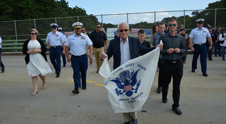 Bradley Finch crosses a Cape Cod bridge holding a Coast Guard Enslgn