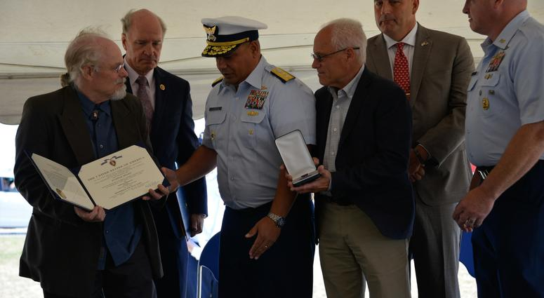 Coast Guard Adm. Andy Tiongson prepares to pose for a photo with Stephen and Bradley Finch