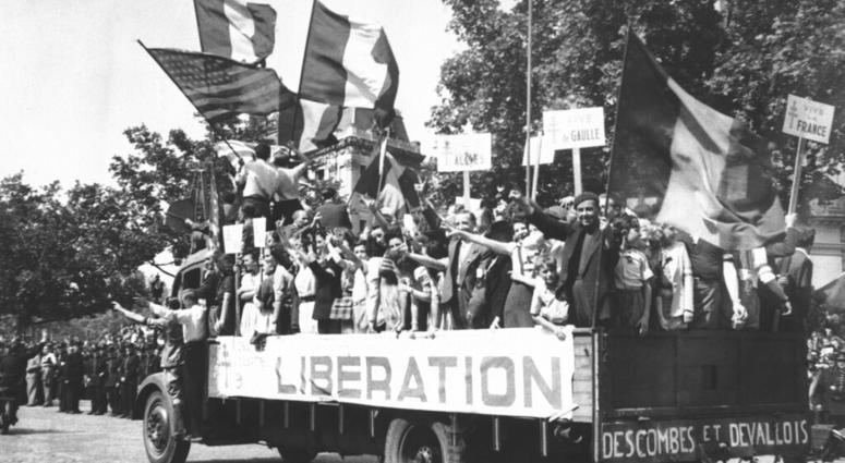 In this Aug. 28, 1944 file photo, a truck load of Parisians waving flags and carrying Vive De Gaulle banners drives through the streets