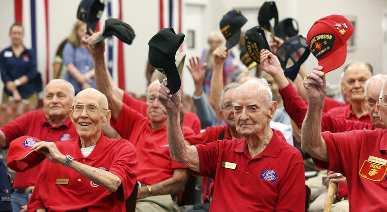 World War II veterans salute with their caps as they pose for a photograph after a ceremony at Joint Base San Antonio-Fort Sam Houston