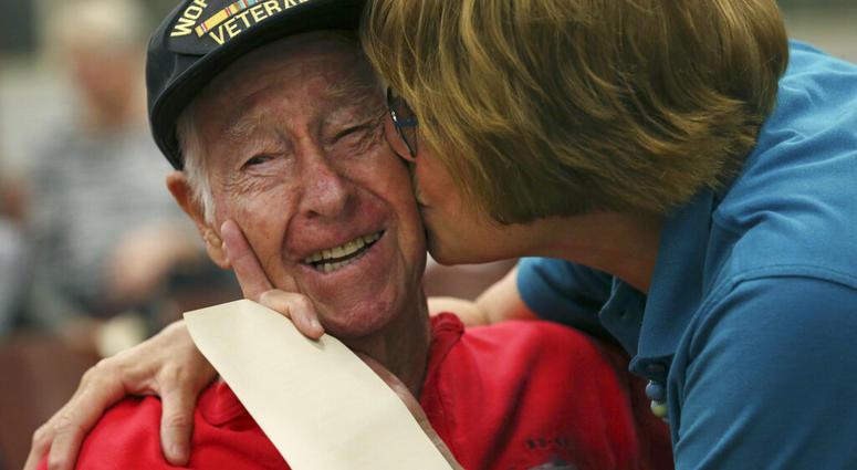 Alamo Honor Flights volunteer Elizabeth Montalvo kisses World War II veteran E.W. King, 94, before a ceremony