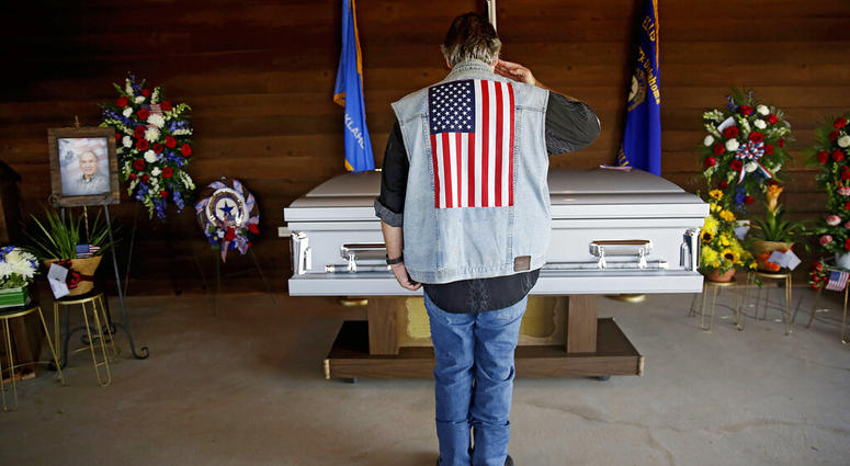 Army veteran Mike Traupman salutes the casket of World War II veteran Herman White
