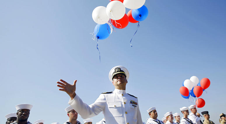 Navy Lieutenant Luke Hosman releases balloons during a funeral service for World War II veteran Herman White
