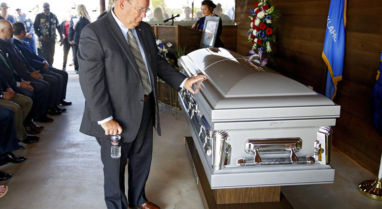 Ben Robinson, Oklahoma Secretary of MIlitary and Veterans Affairs, touches the casket of World War II veteran Herman White