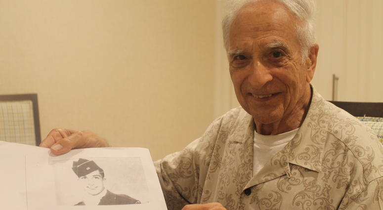 Frank Cohn holding a picture of himself in uniform during World War II.