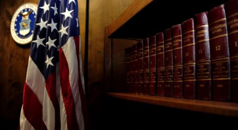 "Volumes of ""Court-Martial Reports"" line the bookshelf located in the courtroom."