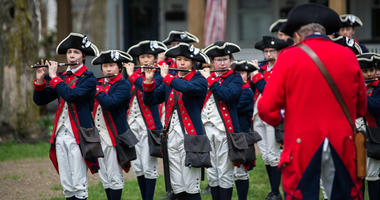 Colonial reenactors prepare to participate in a Patriots' Day parade in Lexington, Mass.