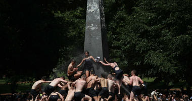 Plebes no more: U.S. Naval Academy Class of 2022 climbs the Herndon Monument.