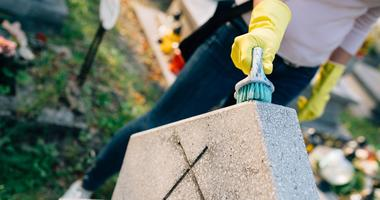Woman cleans a headstone in a cemetary.