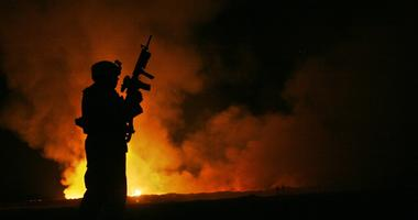 Sgt. Robert B. Brown from Fayetteville, N.C. with Regimental Combat Team 6, Combat Camera Unit watches over the civilian Fire Fighters at the burn pit as smoke and flames rise into the night sky behind him on May 25th, 2007.