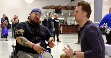 Host Jordan Klepper (right) speaks with a vet at a Valhalla Club event in Killeen, Texas