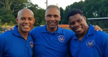 A photo of Air Force veteran Rob Wilkins alongside Yankees legend Mariano Rivera and multi-sport superstar Herschel Walker