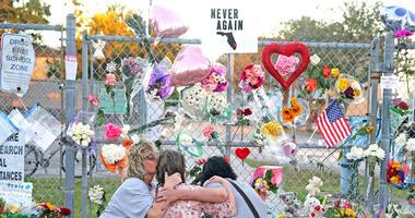 Shari Unger kisses Melissa Goldsmith as Giulianna Cerbono lights candles at a memorial at Marjory Stoneman Douglas High School on Sunday, February 18, 2018.
