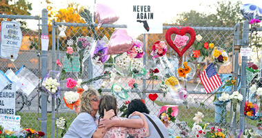 Shari Unger kisses Melissa Goldsmith as Giulianna Cerbono lights candles at a memorial at Marjory Stoneman Douglas High School on Sunday, February 18, 2018.