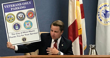 Diaz-Padron hols up veterans parking sign