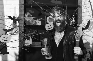 Halloween decor on background Demon with horns and wild face holds black electric guitar.
