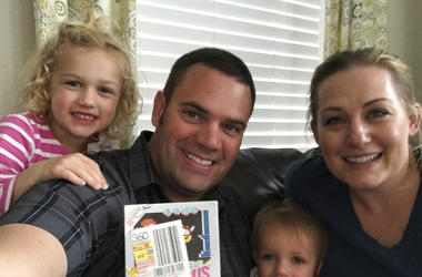 """In this June 15, 2019 photo provided by Heritage Auctions, Scott Amos, along with his wife, Kristy, and daughters Grace, left, and Katie, pose in Reno, Nev., with an unopened copy of a 1987 cult-classic video game """"Kid Icarus."""" The boxed game cartridge, s"""