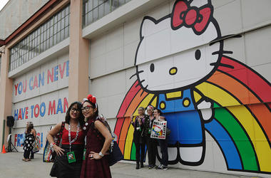 Tina Chinakarn, left, and Julie To, right, take a picture in front of a Hello Kitty mural outside of Hello Kitty Con October 31, 2014 at The Geffen Contemporary at MOCA in Los Angeles, California. Some 25,000 fans are expected to attend Hello Kitty Con be