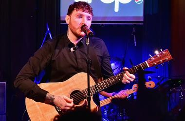 James Arthur performing on stage.