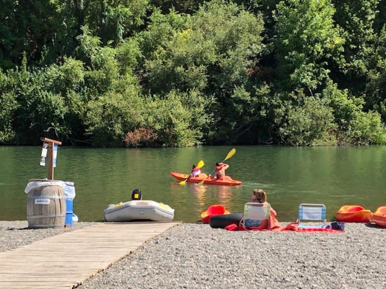 Visitors kayak in the river along Johnson's Beach in Guerneville
