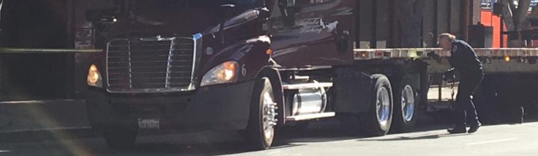 San Francisco police officers examine a truck that was possibly used in a hit and run on Market and Fifth streets on July 18, 2019.