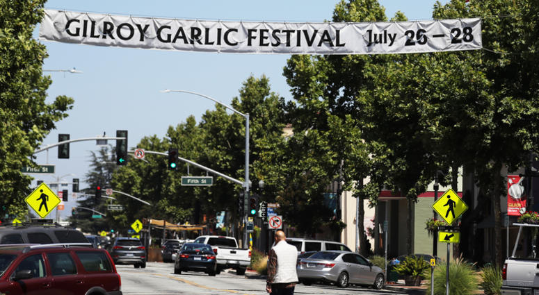 A man walks beneath a sign advertising the nearby Gilroy Garlic Festival after a mass shooting took place at the event yesterday on July 29, 2019 in Gilroy, California.
